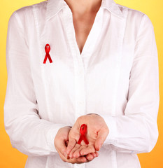 Woman with red ribbon in hands on orange background