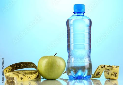 Bottle of water, apple and measuring tape on blue background
