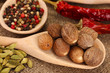 Nutmeg and other spices on sackcloth background