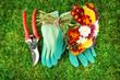Secateurs with flowers on green grass background