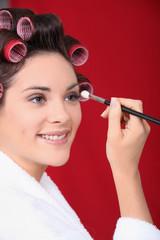 Woman in curlers applying eyeshadow