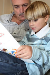 Grandfather and son reading