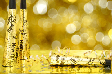 New Years Eve noisemakers with twinkling gold light background