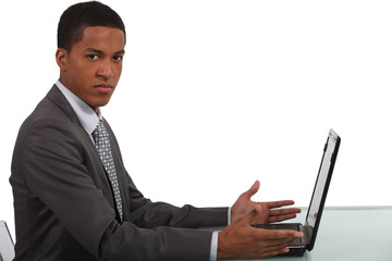 Disgruntled office worker sat with laptop