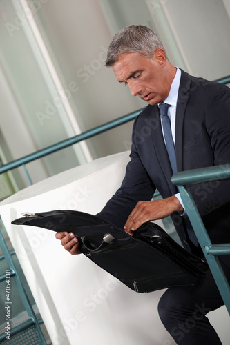 Businessman rummaging thought his briefcase