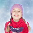 Smiling girl with snow in hands, blue background