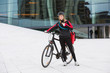 Female Cyclist With Courier Delivery Bag Using Walkie-Talkie