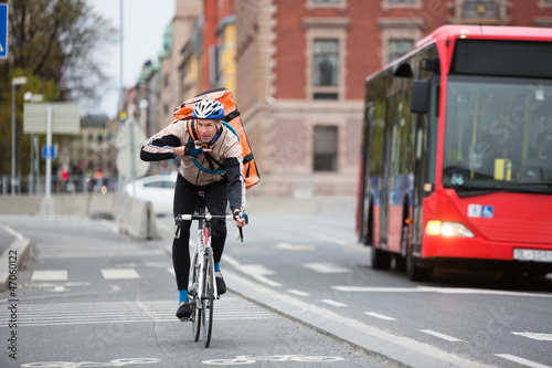 Courier Delivery Man Using Walkie-Talkie While Riding Bicycle On