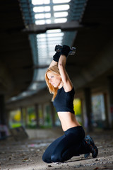 Woman lifting weights in urban setting