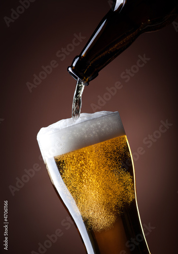 beer glass and bottle on a brown