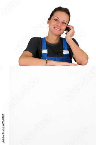 Woman with a cellphone and board left blank for message
