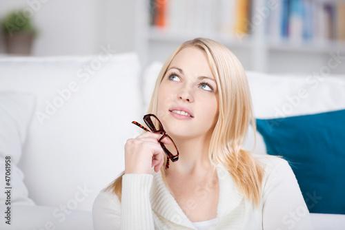blonde frau hält brille in der hand