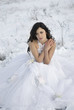 pretty young woman posing in wedding dress  on winter snow