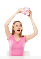 Woman checking piggy bank for money