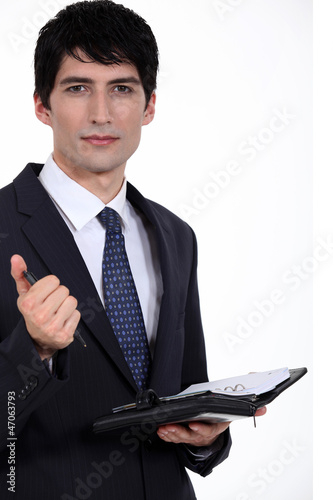 A businessman about to write on his agenda.