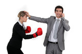 Businesswoman trying to box a man on a phone