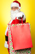 Cheerful Santa holding vibrant colored shopping bags