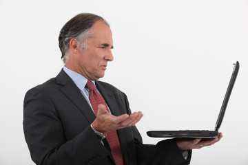 Senior businessman having technical issues with laptop