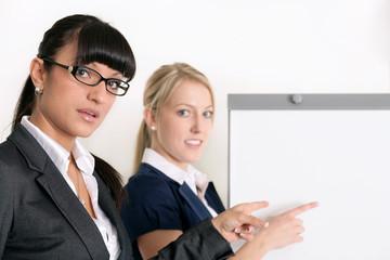 Attraktive Geschäftsfrauen am Flipchart
