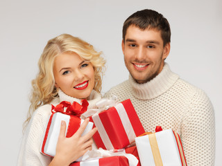 family couple in a sweaters with gift boxes