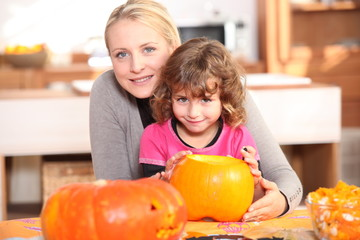 Mother and daughter decorating pumpkins
