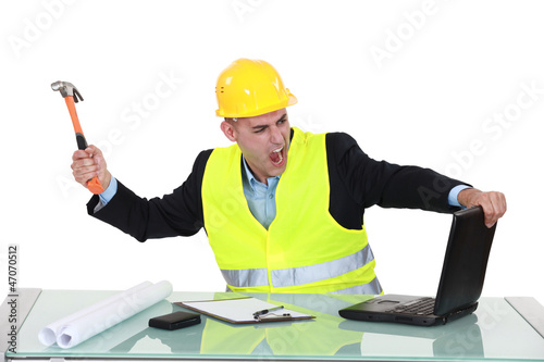 Architect smashing his laptop with hammer