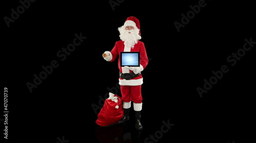 Santa Claus presenting a blank tablet, against black