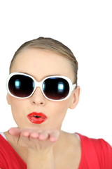 Woman with sunglasses blowing kisses on white background