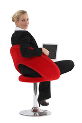 Businesswoman sitting in a funky chair with a laptop
