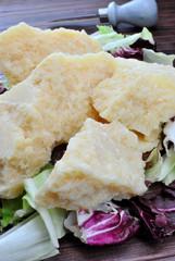 Pezzi di parmigiano su foglie di insalata