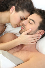 Young couple laid in bed