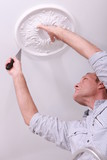 Man putting molding on the ceiling