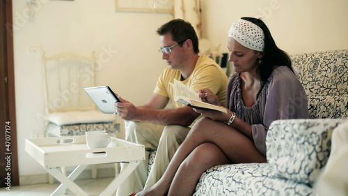 Woman reading book while her boyfriend is using tablet