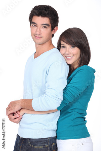 Teenage girl with arms around boyfriend