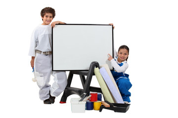 two children dressed in housepainter and a whiteboard