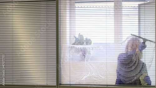 Professional maid cleaning and wiping window in office with soap