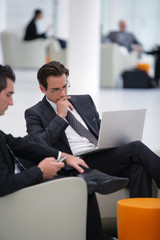 Businessmen waiting in airport lounge