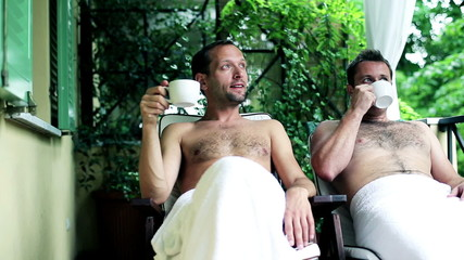 Two guys with cups of tea talking and relaxing in spa resort, ou