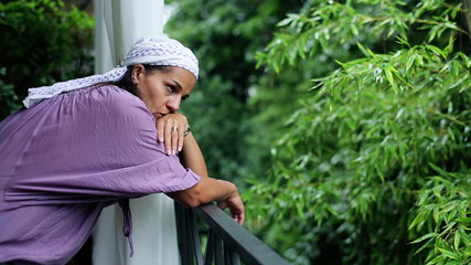 Sad woman standing on balcony