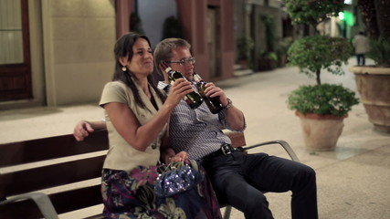 Young drunk couple drinking alcohol on bench, steadicam shot