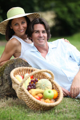 Couple posing with a fruit basket