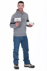 Man holding roll of wallpaper and brush