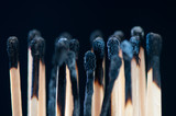 Rows of burnt matches over a black background, macro shot