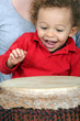 Little boy playing with djembe