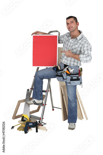 Carpenter proudly standing by equipment