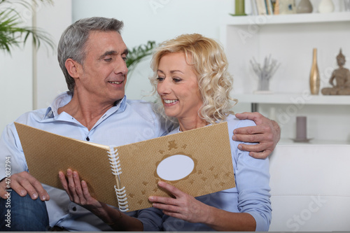 couple sitting on sofa skimming through family album