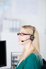 junge frau im büro telefoniert mit headset