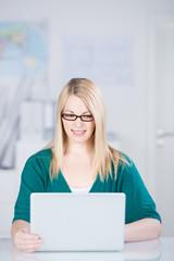 lächelnde junge frau im büro schaut auf laptop