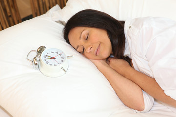 Woman asleep with alarm