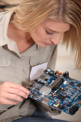 Female computer technician holding circuit board